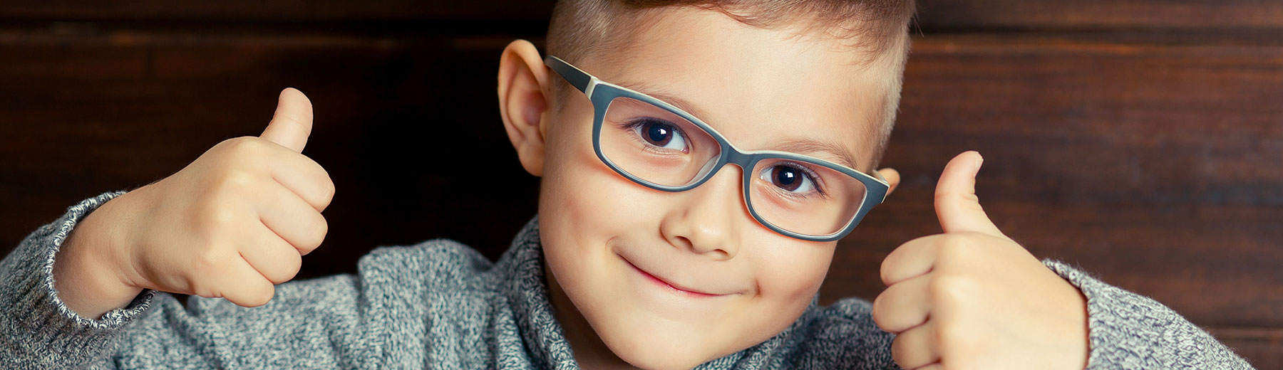young boy child wearing glasses thumbs up
